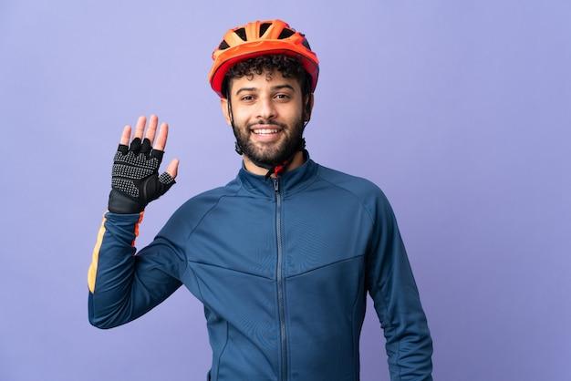 幸せな表情で手で敬礼する紫色の壁に孤立した若いモロッコのサイクリストの男