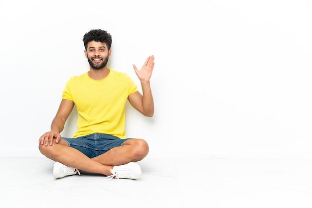 孤立した床に座っている若いモロッコのハンサムな男