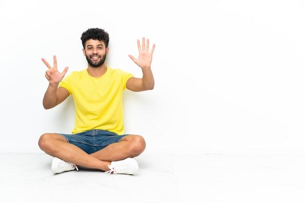 손가락으로 여덟 세 격리 된 배경 위에 바닥에 앉아 젊은 모로코 잘 생긴 남자