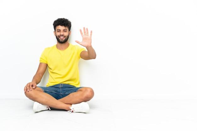 손가락으로 5 세 격리 된 배경 위에 바닥에 앉아 젊은 모로코 잘 생긴 남자