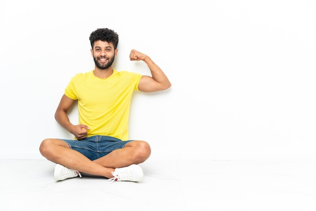 강한 제스처를 하 고 격리 된 배경 위에 바닥에 앉아 젊은 모로코 잘 생긴 남자