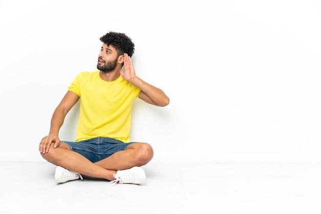 孤立した背景の上に床に座って、耳に手を置いて何かを聞く若いモロッコのハンサムな男