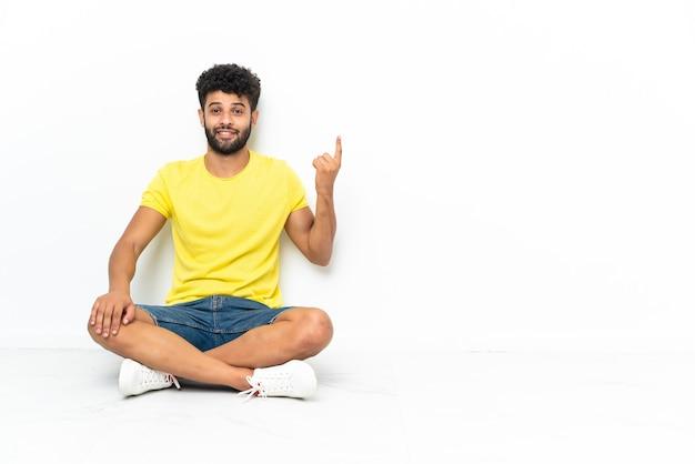 검지 손가락으로 가리키는 격리 된 배경 위에 바닥에 앉아 젊은 모로코 잘 생긴 남자 좋은 아이디어