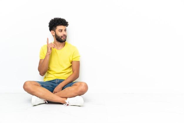 Молодой марокканский красавец сидит на полу на изолированном фоне, думая об идее, указывая пальцем вверх