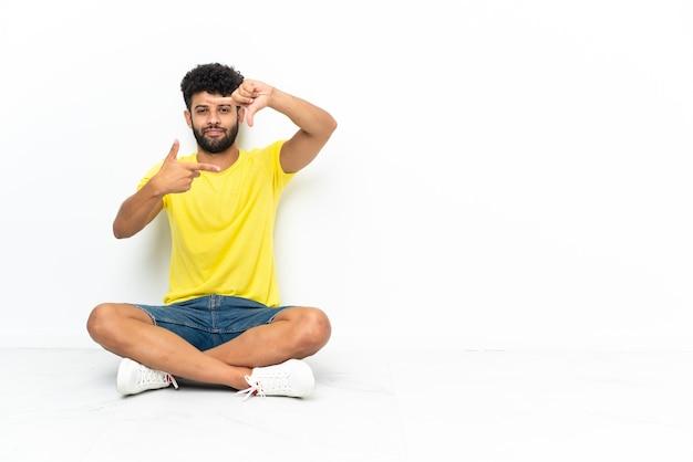 孤立した壁の焦点の顔の上の床に座っている若いモロッコのハンサムな男。フレーミングシンボル