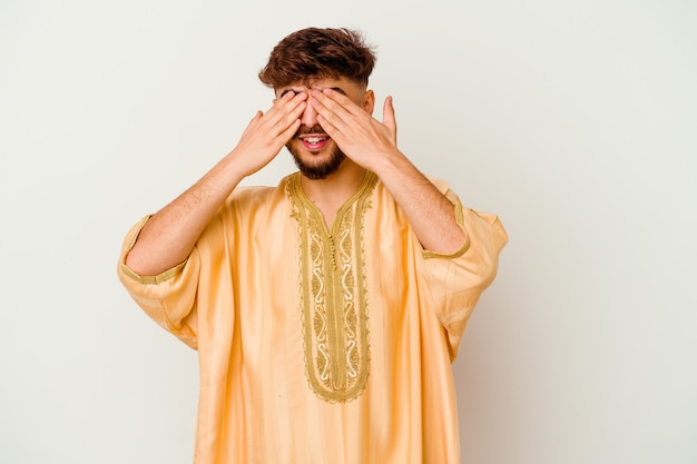 Young moroccan man   afraid covering eyes with hands.