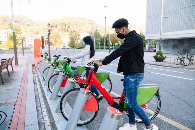 A young moroccan man and a caucasian girl are picking up a rented electric bicycle in the street bicycle parking lot and wearing a face mask for the 2020 coronavirus pandemic.