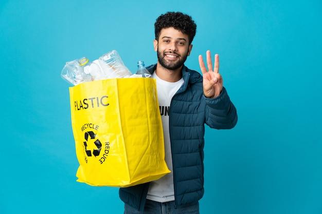 ペットボトルでいっぱいのバッグを持って幸せにリサイクルし、指で3つを数える若いモロッコ人男性