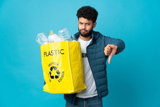 孤立したリサイクルのためにペットボトルでいっぱいのバッグを保持している若いモロッコ人