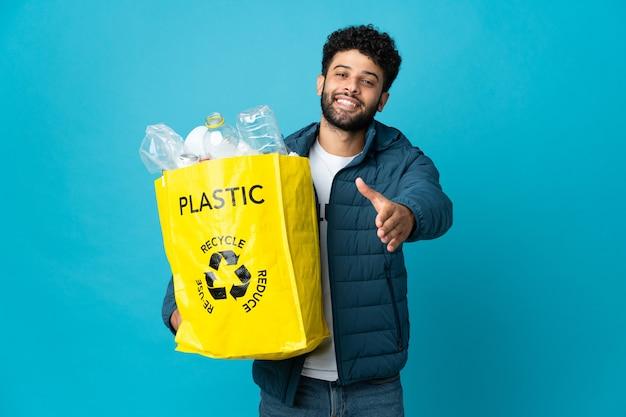고립 된 재활용 플라스틱 병의 전체 가방을 들고 젊은 모로코 남자