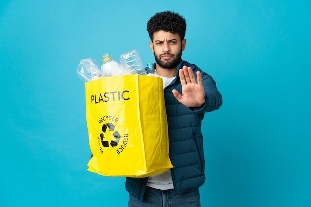 ペットボトルがいっぱい入ったバッグを持って、孤立した壁をリサイクルして停止ジェスチャーをするモロッコの若者