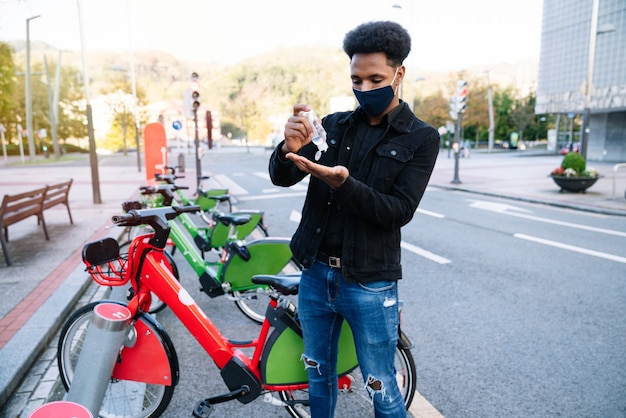 A young moroccan man is pouring hydroalcoholic gel on his hands to pick up a rented electric bicycle in the street bicycle parking lot and is wearing a face mask for the coronavirus pandemic