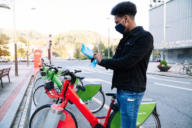 A young moroccan man is putting on latex gloves to pick up a rented electric bicycle in the street bicycle parking lot and is wearing a face mask for the 2020 coronavirus pandemic.