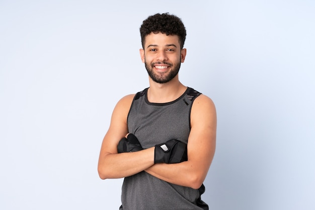 Young moroccan man isolated on blue wall happy and smiling
