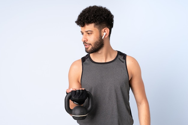 Young moroccan man isolated on blue wall making weightlifting with kettlebell