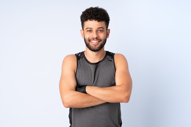 Young moroccan man isolated on blue wall with arms crossed
