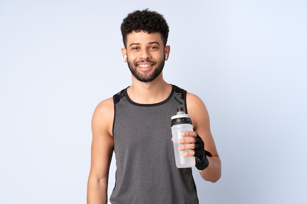 Young moroccan man isolated on blue wall with sports water bottle