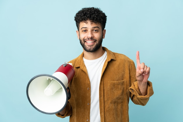 Young moroccan man isolated holding a megaphone and pointing up a great idea
