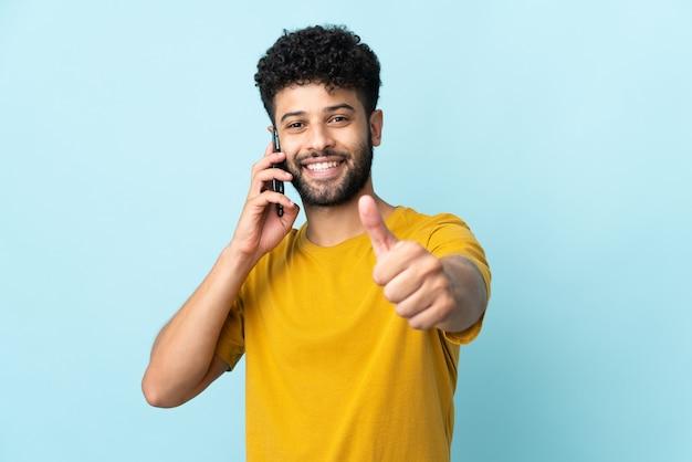 Молодой марокканский мужчина изолирован на синей стене, разговаривает с мобильным телефоном и показывает палец вверх