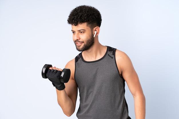 Молодой марокканец изолирован на синей стене, делая тяжелую атлетику