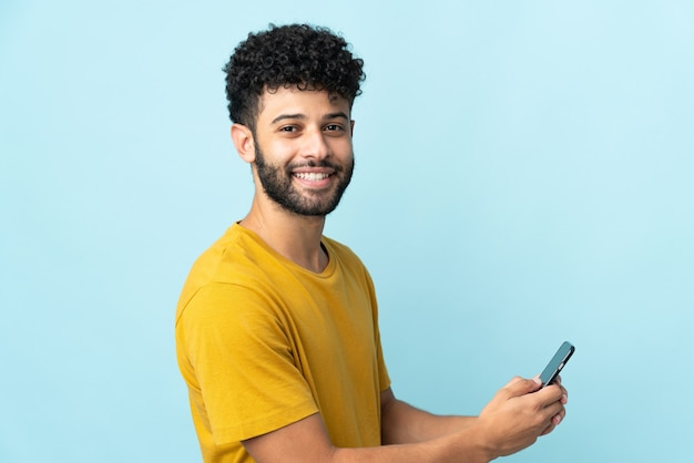 Молодой марокканский мужчина изолирован на синей стене, отправляя сообщение или электронное письмо с мобильного телефона