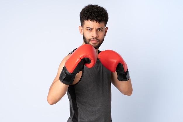 Молодой марокканский мужчина изолирован на синей стене в боксерских перчатках