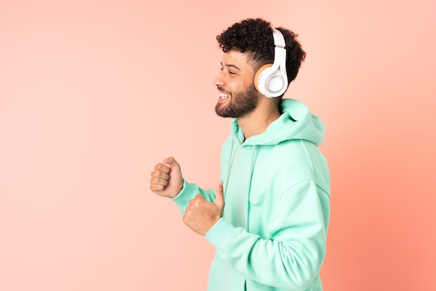 Молодой марокканский мужчина изолирован на розовом фоне, слушает музыку и танцует