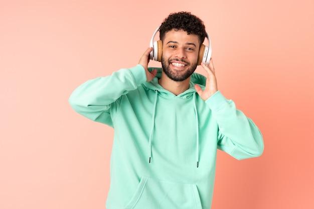 ピンクのリスニング音楽に孤立した若いモロッコ人 Premium写真