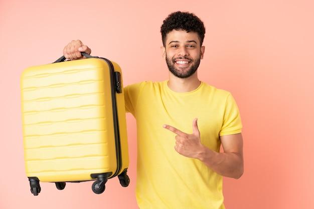 여행 가방 휴가에 분홍색 벽에 고립 된 젊은 모로코 남자