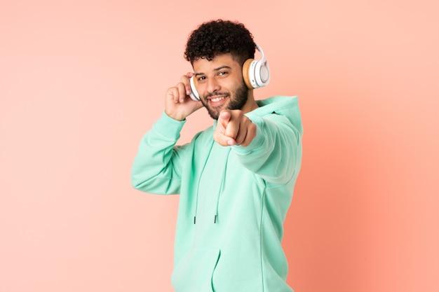 Молодой марокканский мужчина изолирован на розовой стене, слушает музыку и указывает вперед