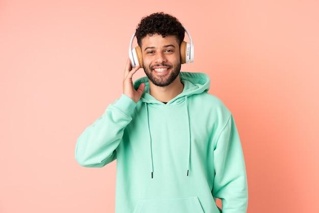 Молодой марокканец изолирован на розовой стене, слушающей музыку