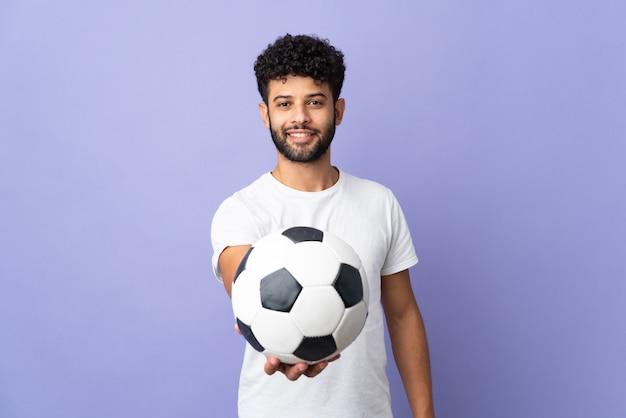 Молодой марокканский мужчина, изолированные на фиолетовом фоне с футбольным мячом