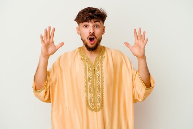 승리 또는 성공을 축 하하는 흰색에 고립 된 젊은 모로코 남자, 그는 놀라게 하 고 충격.
