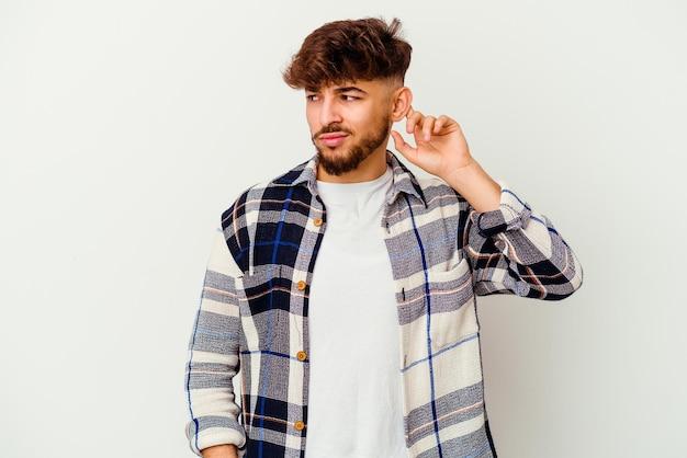 若いモロッコ人男性は、指で耳を覆っている白い上に孤立し、大声で周囲にストレスを感じ、必死になりました。