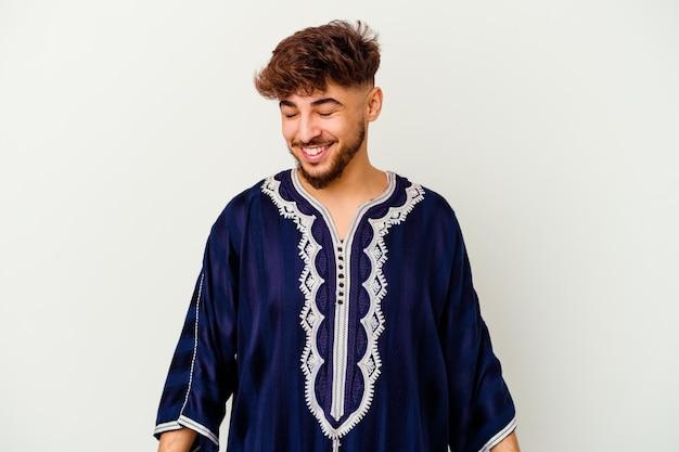 白いで孤立した若いモロッコ人は笑って目を閉じ、リラックスして幸せを感じます。
