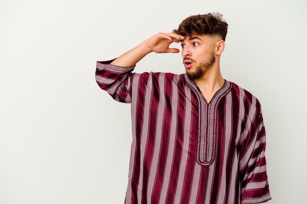 이마에 손을 멀리 유지 찾고 흰색에 고립 된 젊은 모로코 남자.