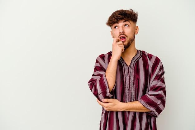흰색에 고립 된 젊은 모로코 남자 복사본 공간을 찾고 뭔가 대해 편안한 생각.