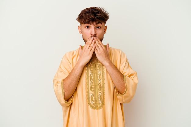 흰색에 고립 된 젊은 모로코 남자는 새로운 것을 발견하고 싶어 손으로 입을 덮고 충격을 받았습니다.
