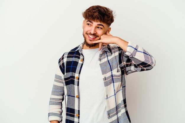 젊은 모로코 남자 손가락으로 휴대 전화 제스처를 보여주는 흰색 절연.
