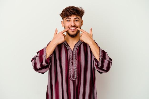 입에 손가락을 가리키는 흰색 미소에 고립 된 젊은 모로코 남자.