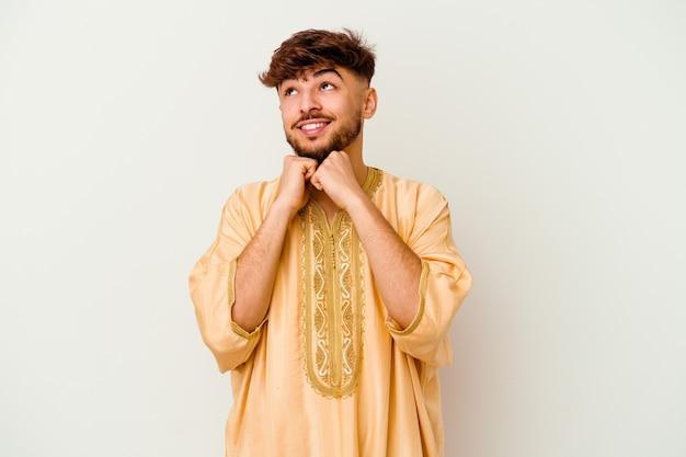 Молодой марокканский мужчина, изолированный на белой стене, держит руки под подбородком, счастливо смотрит в сторону.