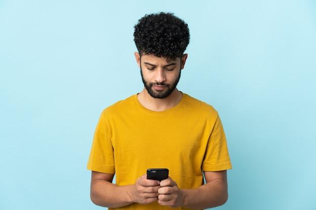 Молодой марокканский мужчина изолирован с помощью мобильного телефона
