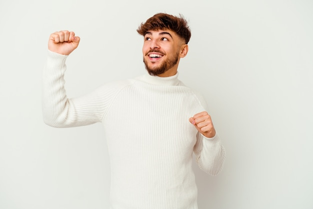 Young moroccan man isolated on white dancing and having fun.