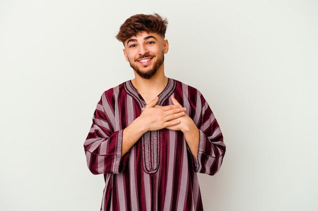 Young moroccan man isolated on white has friendly expression, pressing palm to chest