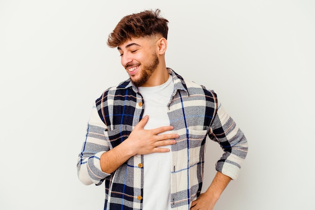 Young moroccan man isolated on white laughing keeping hands on heart, concept of happiness.