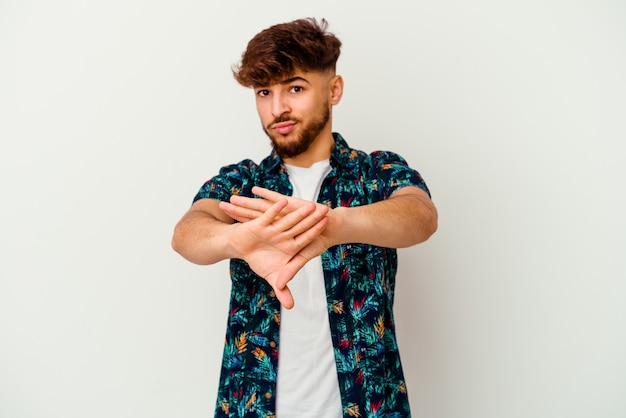Young moroccan man isolated on white wall doing a denial gesture