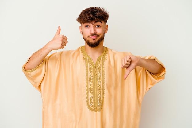 Молодой марокканский мужчина показывает палец вверх и палец вниз, сложно выбрать концепцию