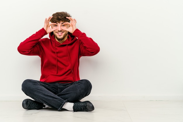 Young moroccan man sitting on the floor isolated on white keeping eyes opened to find a success opportunity.