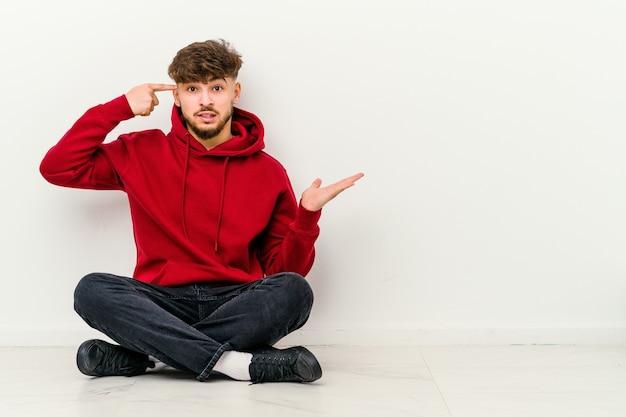 들고와 손에 제품을 보여주는 바닥에 앉아 젊은 모로코 남자.