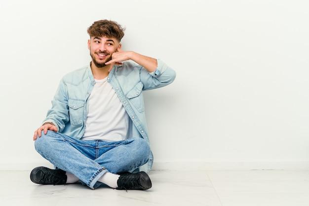 指で携帯電話の呼び出しジェスチャーを示す白で隔離の床に座っている若いモロッコ人男性。